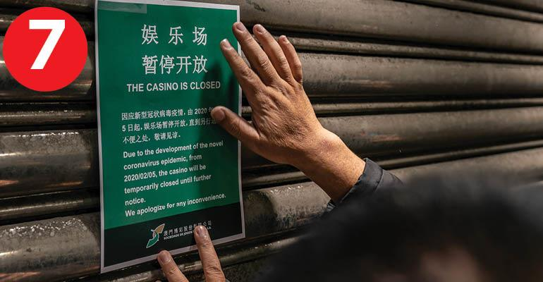 An employee puts up a closing notice on the gate of the main entrance of Casino Lisboa after its closing