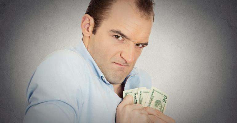 Greedy male banker clutching dollar bills