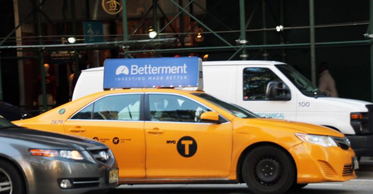 A taxi with a Betterment ad on the hood.