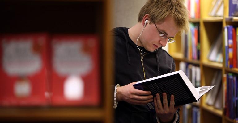 college student reading book bookstore