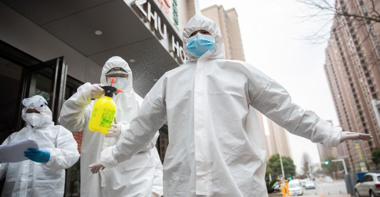 A volunteer disinfects a colleague outside a hotel where recovered patients spend a 14-day quarantine in Wuhan in China's central Hubei province