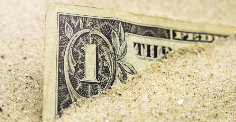 dollar buried in sand