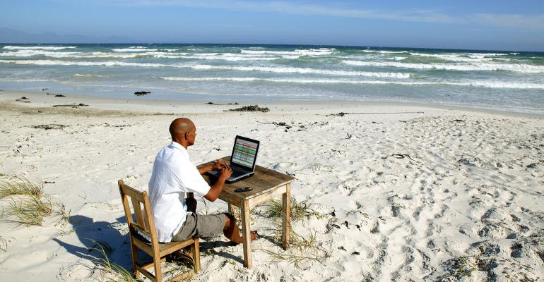 A man working on a laptop at the beach.