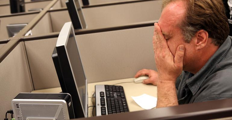 man wiping eyes at computer