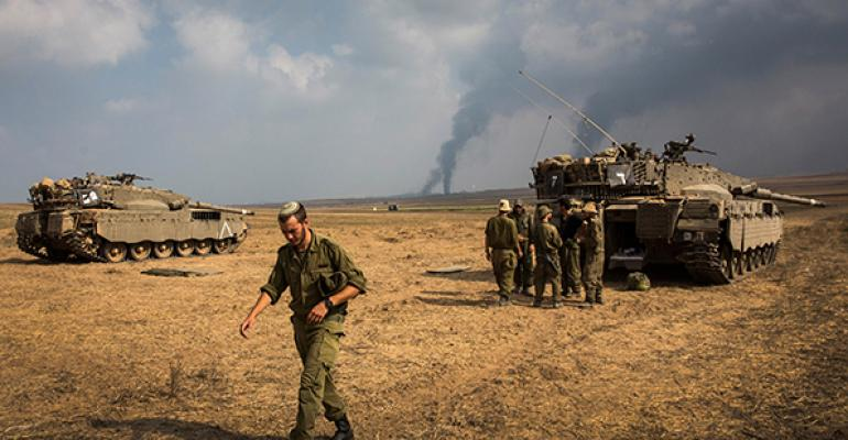 Israeli soldiers stand near their tank while smoke due to airstrikes and shelling rises from the Gaza Strip