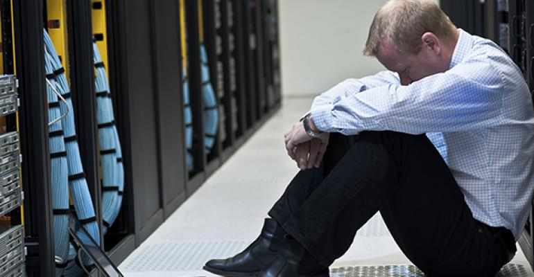 A man sitting in an aisle of mainframe computers.