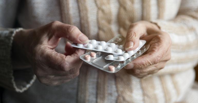 elderly woman hands pills